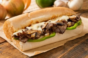 A delicious oven bake steak and cheese submarine sandwich with mushrooms, green peppers, and onion.